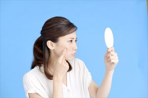 鏡でシミをチェックする女性