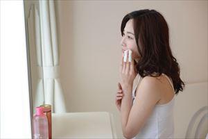 鏡でteateaふきとり化粧水の効果を確認する女性