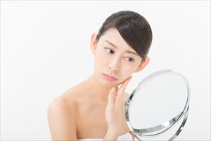 鏡で肌を見てる女性