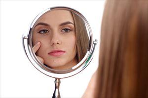 鏡を見てケアする女性